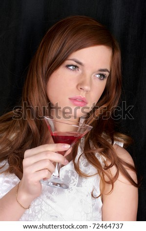 Closeup portrait of beautiful young woman with red cocktail - stock photo