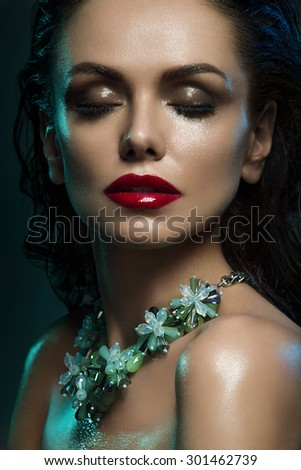Closeup portrait of beautiful young woman with wet skin, and glossy red lips wearing green crystal necklace over dark background - stock photo