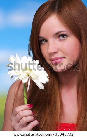 Closeup portrait of beautiful young woman with white flower - stock photo