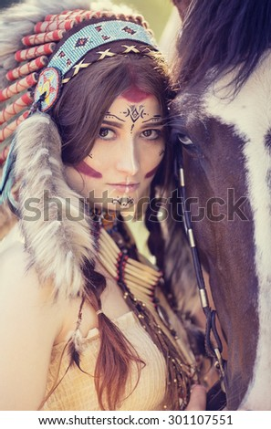 Closeup portrait of beautiful young women in the national Indian headdress with a horse