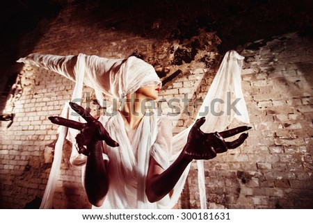 Closeup portrait of blind insane creature in cocoon stretching black hands towards watcher at bricks wall background. Concept of horror movie. - stock photo