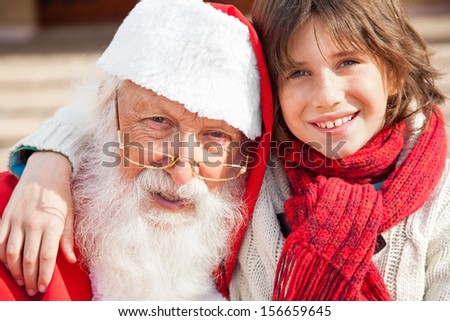 Closeup portrait of boy and Santa Claus smiling outdoors - stock photo