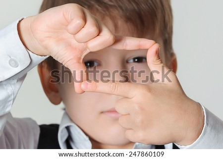 closeup portrait of boy gesturing finger frame and looking through it, selective focus - stock photo