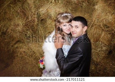 Closeup portrait of bride and groom hugging on hay at stable - stock photo