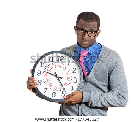 Closeup portrait of business man, student, sad, stressed employee holding clock, pressured by lack, running out of time, late for meeting, deadline isolated on white background. Emotions, expressions - stock photo