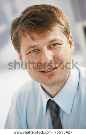 Closeup portrait of businessman in office, looking at camera, smiling.? - stock photo