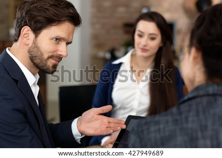 Closeup portrait of businessman talking to colleagues, using tablet. - stock photo