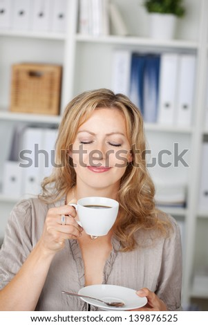 Closeup portrait of businesswoman holding coffee cup in office - stock photo