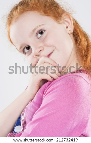 Closeup Portrait of Caucasian Beautiful Curious Redhaired Little Girl. Looking Up Against White Background. Vertical Image - stock photo