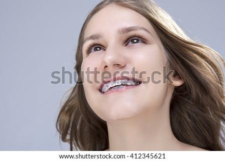 Closeup Portrait of Caucasian Female Teenage Girl With Teeth Brackets. Posing in Studio. Horizontal Image Composition - stock photo