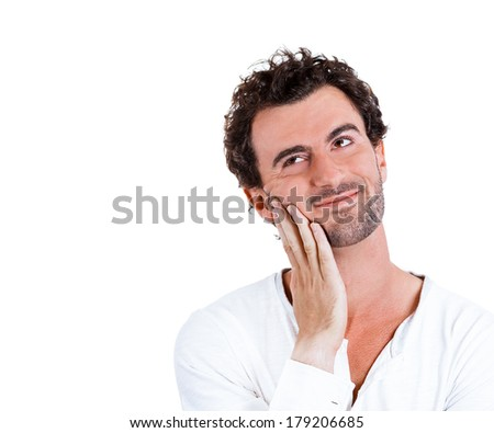 Closeup portrait of charming upbeat smiling joyful happy young man looking upwards with hand on cheek daydreaming, isolated on white background. Positive emotion facial expression feelings, attitude