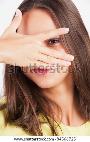Closeup portrait of charming young woman peeking though her fingers - stock photo