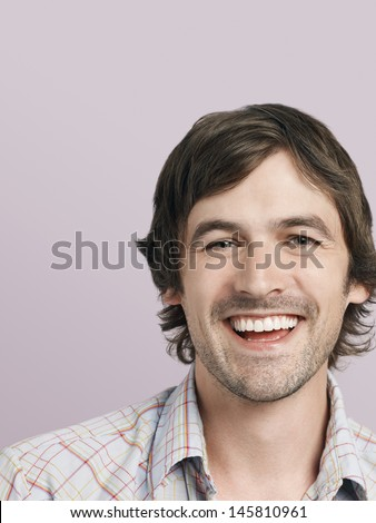 Closeup portrait of cheerful young man isolated on colored background - stock photo