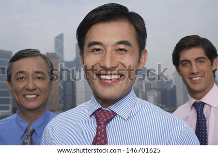 Closeup portrait of confident multiethnic businessmen with cityscape in background - stock photo