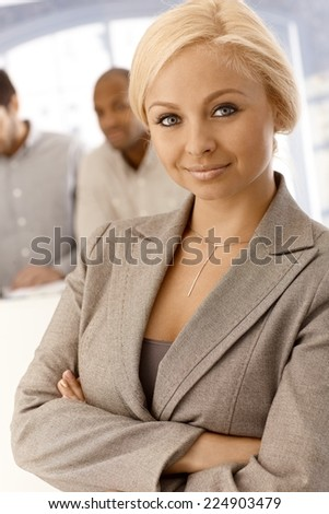 Closeup portrait of confident young businesswoman standing arms crossed, looking at camera. - stock photo