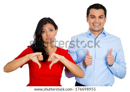 Closeup portrait of conflict couple, man woman. One excited happy smiling optimistic, showing thumbs up, other serious concerned unhappy thumbs down, isolated on white background. Emotion contrasts - stock photo