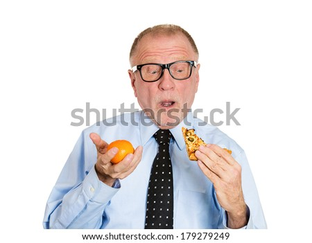 Closeup portrait of confused senior mature man in big black glasses trying to decide what to eat, unhealthy pizza or nutritious orange, isolated white background. Food diet option situations, dilemma - stock photo