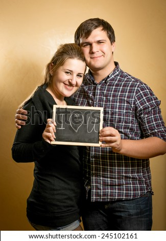 """Closeup portrait of couple in love holding blackboard with """"I love you"""" written by chalk - stock photo"""