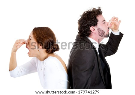Closeup portrait of couple man woman standing back to back pinching noses, dislike, disgusted by each other, isolated on white background. Negative human face expressions, emotions, reaction, attitude - stock photo