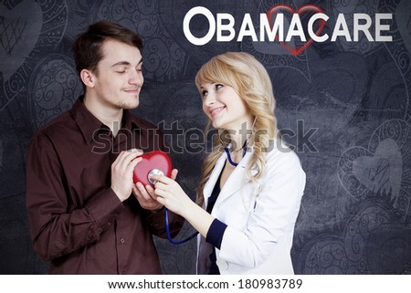 Closeup portrait of couple, smiling female blonde doctor with stethoscope listening to red heart held in hands by happy man student employee isolated grey background. Obamacare, universal health plan - stock photo
