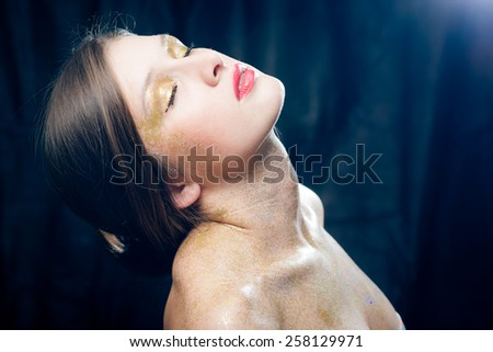 Closeup portrait of covered in shining make up sexy beautiful young woman with eyes closed relaxing on black background