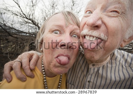 Closeup portrait of crazy elderly couple outdoors sticking out tongues - stock photo