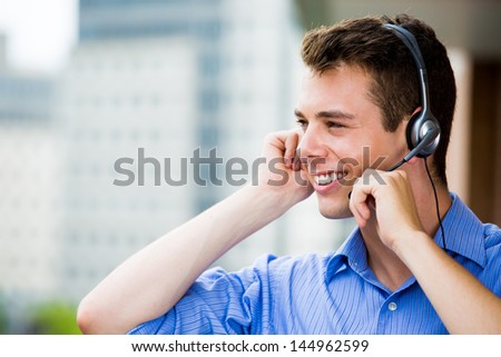 Closeup portrait of customer service representative or call center agent or support or operator with headset on outside balcony, isolated on outside background with trees - stock photo