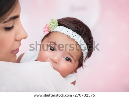 Closeup portrait of cute adorable little baby girl peeking over his shoulder mother, wearing nice head accessory, happy young family concept - stock photo