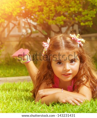 Closeup portrait of cute arabic baby girl lying down on green grass field on backyard, carefree lifestyle, happy childhood concept - stock photo