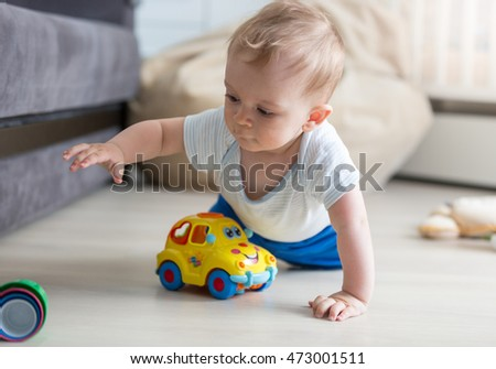 Closeup portrait of cute baby boy crawling on floor and playing with toy car