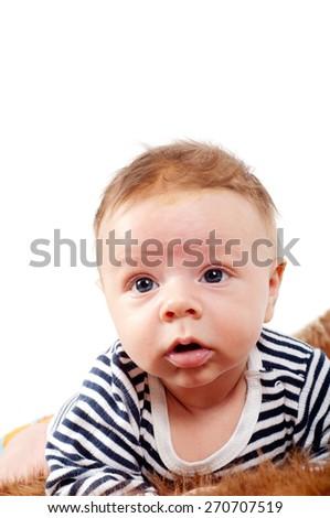 Closeup portrait of cute baby boy lying on fur - stock photo