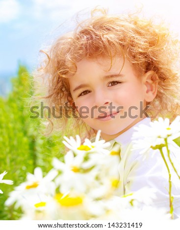 Closeup portrait of cute baby boy with beautiful curly hair on daisy field in sunny day, summer time concept - stock photo