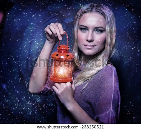 Closeup portrait of cute blond female holding in hands red antique lantern, festive starry night, Christmas celebration concept - stock photo