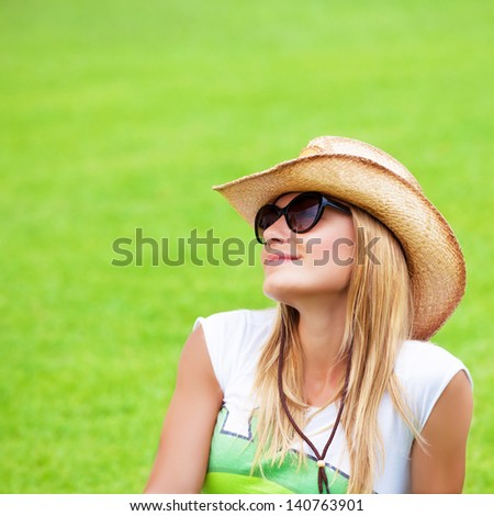 Closeup portrait of cute blond female wearing sunglasses and straw hat sitting down on green grass, having fun outdoors, summer vacation concept - stock photo
