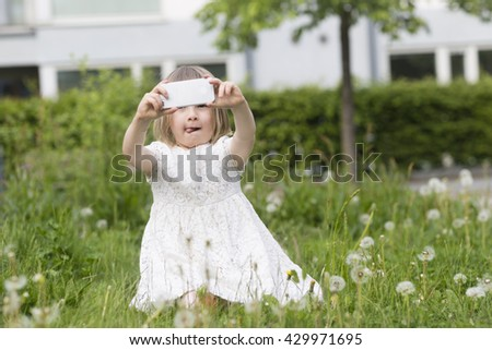 closeup portrait of cute blond girl in preschool age sitting in green grass and holding and playing with mobile phone outdoors, taking photos with it - stock photo
