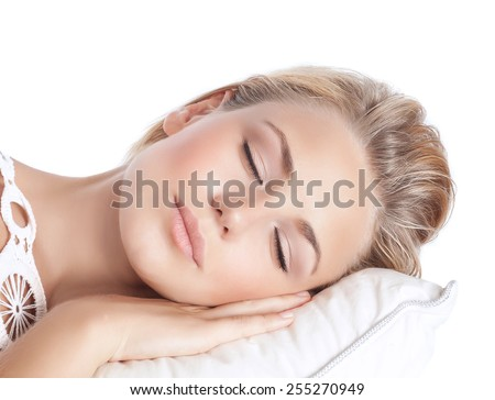 Closeup portrait of cute blond serene girl sleeping, attractive gentle female with closed eyes lying down on the pillow isolated on white background, peace and harmony concept - stock photo