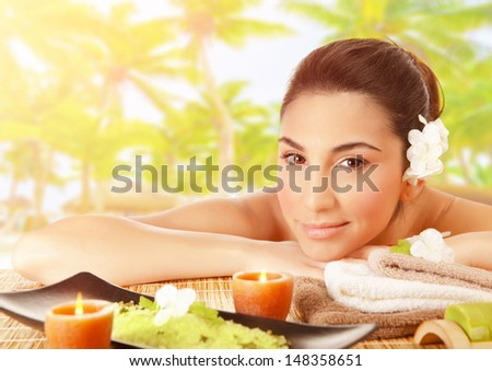 Closeup portrait of cute brunet girl lying down on massage table outdoors, tropical beach, luxury spa resort, alternative therapy, summer relaxation concept - stock photo
