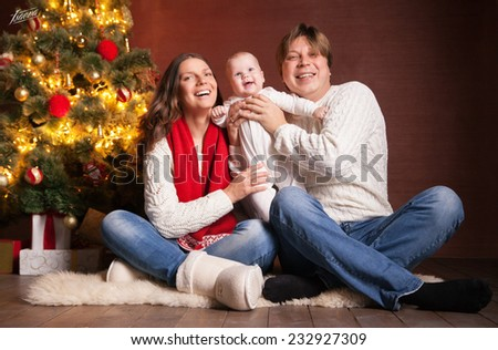 Closeup portrait of cute cheerful family near Christmas tree at home, happy parents with baby celebrate New Year holiday, love concept - stock photo