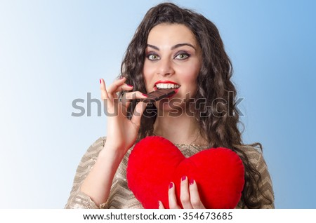 Closeup portrait of cute, curly hair brunette eating chocolate and holding plush heart  - stock photo