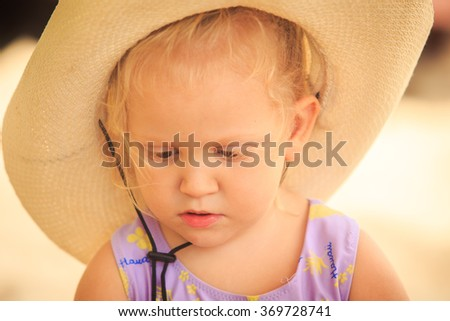 closeup portrait of cute European little blond girl in hat looking downward against sand - stock photo