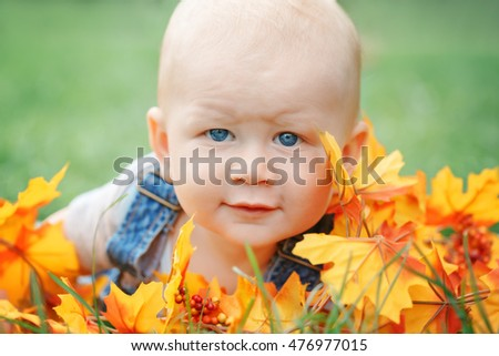 Closeup portrait of cute funny adorable blond Caucasian baby boy with blue eyes in tshirt and jeans romper lying on grass field meadow, yellow autumn fall leaves. Halloween, Thanksgiving.