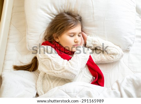 Closeup portrait of cute girl in scarf and sweater sleeping at bed - stock photo