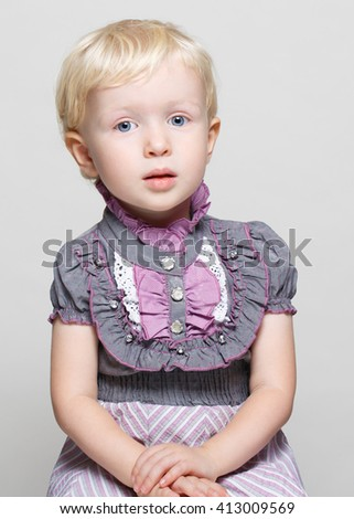 Closeup portrait of  cute girl with blonde hair and blue eyes in vintage retro victorian gothic dress posing sitting in studio looking in camera, light white pure plain background, halloween concept - stock photo