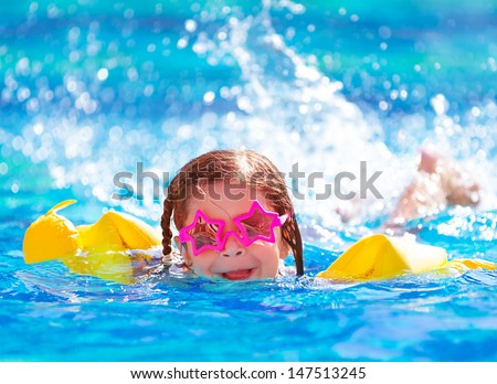 Closeup portrait of cute little arabic girl swimming in the pool, happy child having fun in water, beach resort, summer vacation and holidays concept - stock photo