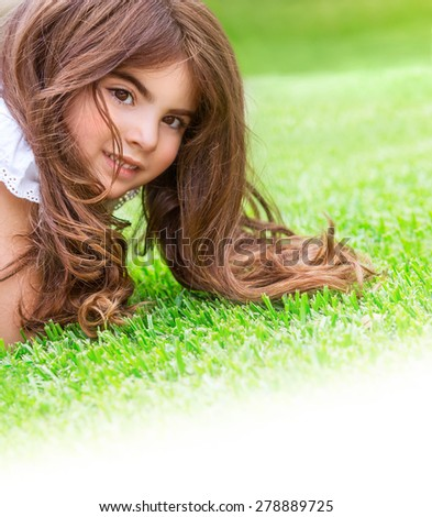 Closeup portrait of cute little girl lying down fresh green grass field, having fun outdoor on backyard, happy childhood concept, white copy space - stock photo