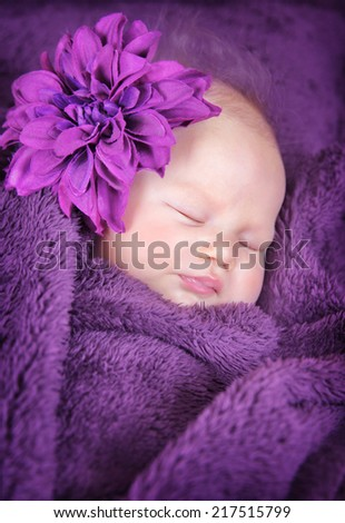 Closeup portrait of cute little newborn baby sleeping at home covered in purple blanket and wearing big stylish flower accessories, innocence concept  - stock photo