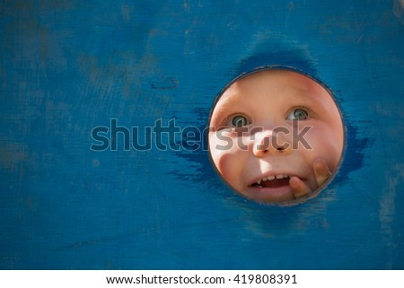 Closeup portrait of cute little toddler boy looking into blue wooden frame at playground. Curiosity, exploration and leaning. Activities for children outdoors. Preschool daycare. Small boy playing - stock photo