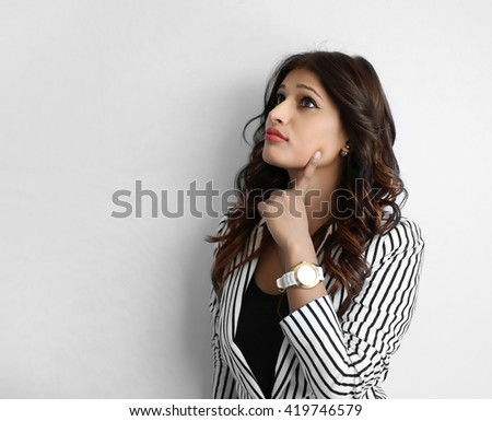 Closeup portrait of cute pretty smiling young indian business woman thinking hand on chin looking up having an idea, isolated on white background. - stock photo