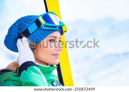 Closeup portrait of cute skier girl looking far away, wearing special sportive mask and holding in hands ski equipment, active lifestyle, enjoying winter vacation concept