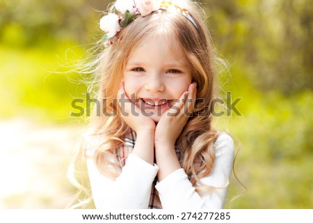 Closeup portrait of cute smiling kid girl 3-4 year old outdoors. Summer time. Freshness.  - stock photo